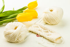 Roll of white soft knitting yarn, knitting mittens and yellow tu Stock Image