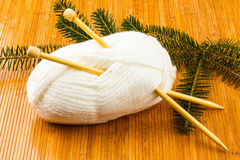Roll of white soft knitting yarn and yew branch Royalty Free Stock Image
