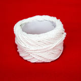 Roll of white string on a red fabric. Stock Photography