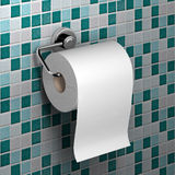Roll of white toilet paper. Hanging on a chrome toilet roll holder on an mosaic tile background Royalty Free Stock Photo