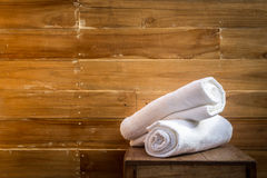 Roll of white towel on table in wooden room Royalty Free Stock Image