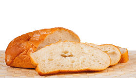Roll of white white bread and three cut off chunks Royalty Free Stock Photography