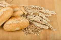 Roll on wooden table with ears of wheat grain Stock Photo
