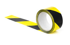 Yellow and black caution tape. Roll of yellow and black caution tape on a white background Royalty Free Stock Photos