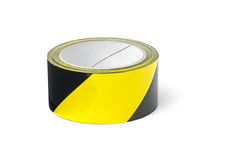 Roll of yellow and black warning tape. On a white background Royalty Free Stock Image