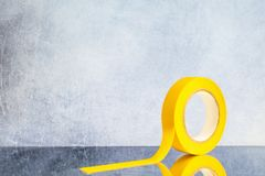 Roll yellow electrical tape on a gray backround royalty free stock image