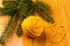 Roll of yellow soft knitting yarn and yew branch Stock Photos