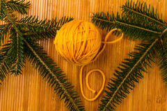 Roll of yellow soft knitting yarn and yew branch Stock Photo