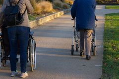 rollator και αναπηρική καρέκλα με τον πρεσβύτερο στο ιστορικό πάρκο στοκ φωτογραφίες με δικαίωμα ελεύθερης χρήσης