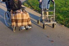 rollator y silla de ruedas con el mayor en el parque histórico imagen de archivo libre de regalías