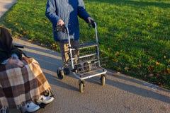 rollator y silla de ruedas con el mayor en el parque histórico foto de archivo