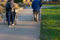 rollator y silla de ruedas con el mayor en el parque histórico imagenes de archivo