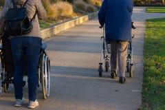 rollatoren och rullstolen med pensionären på historiskt parkerar royaltyfria foton