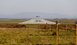 Rollbahn des Flughafens Flugzeug startet Einige Scheinwerfer im Vordergrund für Nachtbeleuchtung Luftfahrt und Transport stockbild