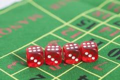 Rolle der roten Würfel auf einem Spieltisch Lizenzfreies Stockfoto
