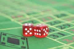 Rolle der roten Würfel auf Spieltisch im Kasino Stockfoto