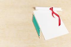 Rolle des Papiers mit einem roten Band und Bleistiften Lizenzfreie Stockfotos