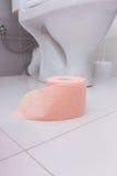 Rolle des Toilettenpapiers auf dem Boden eines Badezimmers Stockfotografie