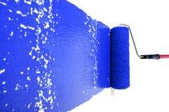 Rolle mit blauem Lack auf weißer Wand Lizenzfreies Stockfoto