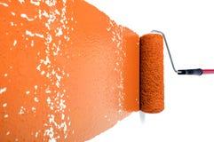 Rolle mit orange Lack auf weißer Wand Stockfotos