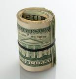 Rolle von $20 Dollarscheinen auf weißer Tabelle Stockfotografie