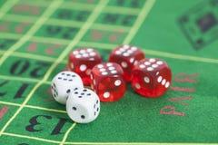 Rolle von roten und weißen Würfeln auf Spieltisch Stockbild