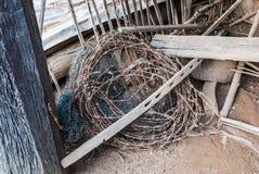 Rolle von Rusty Barbed Wire und von schmutzigem Nylonnetz Stockfotos
