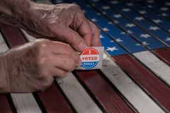 Rolle von wählte mir heute Papieraufkleber auf US-Flagge mit der Hand, die ein entfernt lizenzfreie stockfotografie