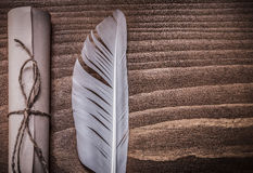 Rolled antique document plume on wooden board Royalty Free Stock Photos