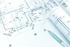 Rolled architectural blueprints and pencil on floor plan drawing. Rolled architectural blueprints and mechanic pencil on floor plan drawing royalty free stock photo