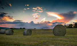Rolled bales of hay are seen on a rolling hill during a magnificent sunset Stock Images