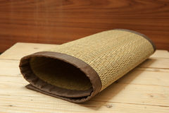 Rolled bamboo place mats on wood background Royalty Free Stock Photos