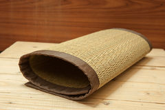 Rolled bamboo place mats on wood background Stock Images