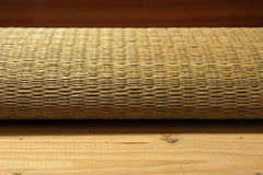 Rolled bamboo place mats on wood background Stock Photography