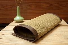 Rolled bamboo place mats on wood background Stock Image