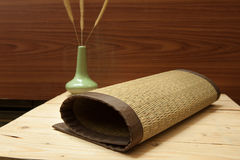 Rolled bamboo place mats on wood background Royalty Free Stock Image
