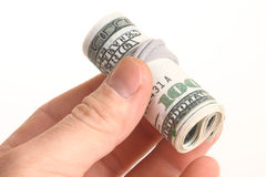 Rolled banknotes. Some notes of 100 dollars, rolled in a hand Royalty Free Stock Images
