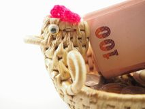 Rolled banknotes on basket with chicken shape Royalty Free Stock Images