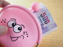 Rolled banknotes in pink purse with happy smiling, easy drawing on handbag Royalty Free Stock Image