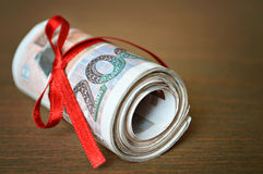 Rolled banknotes tied with red ribbon Stock Image