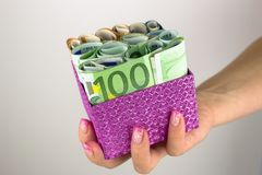 A woman with a manicure holding a gift box full of euro banknotes. royalty free stock photography