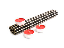 Rolled black bamboo mat and three red candles Royalty Free Stock Photos