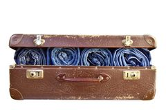 Rolled blue jeans pants in old suitcase isolated stock photos