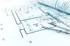Rolled blueprints, ruler and drawing compass on architectural pr Stock Image