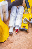 Rolled blueprints yellow hardhat red pencil level Royalty Free Stock Image