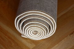 Rolled carpet. On a wooden floor Stock Photo