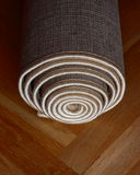 Rolled carpet. On a wooden floor Stock Photography