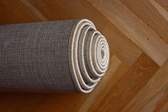 Rolled carpet. On a wooden floor Royalty Free Stock Photo