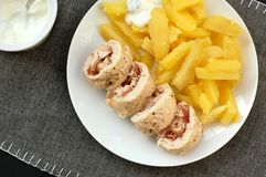 Rolled chicken fillet with prosciuto and mozzarela with pototoes on white plate on grey cloth Royalty Free Stock Photography