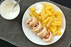 Rolled chicken fillet with prosciuto and mozzarela with pototoes on white plate on grey cloth Royalty Free Stock Photos